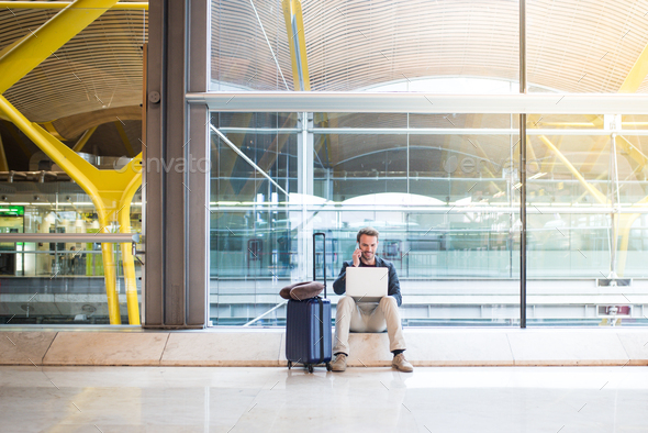 man sitting at the airport using laptop and mobile phone next to - Stock Photo - Images