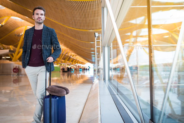 man front walking at the airport using mobile phone - Stock Photo - Images
