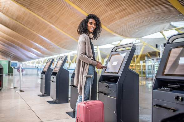 happy woman using the check-in machine at the airport getting th - Stock Photo - Images
