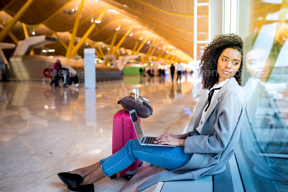 woman working with laptop at the airport waiting at the window - Stock Photo - Images