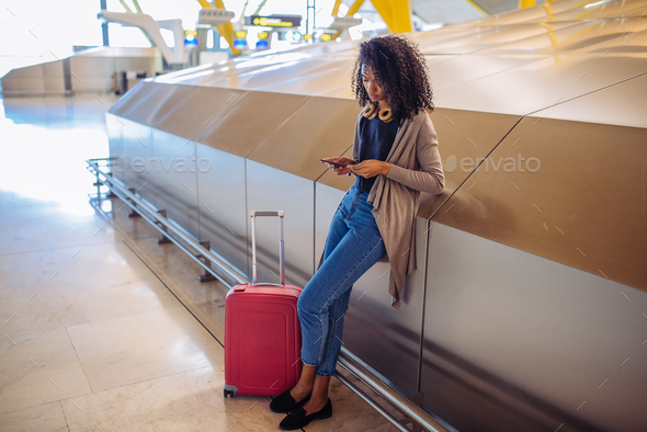 woman waiting her flight using mobile phone at the airport - Stock Photo - Images