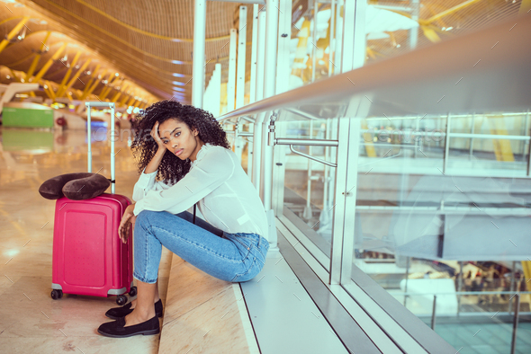 Woman sad and unhappy at the airport with flight canceled - Stock Photo - Images