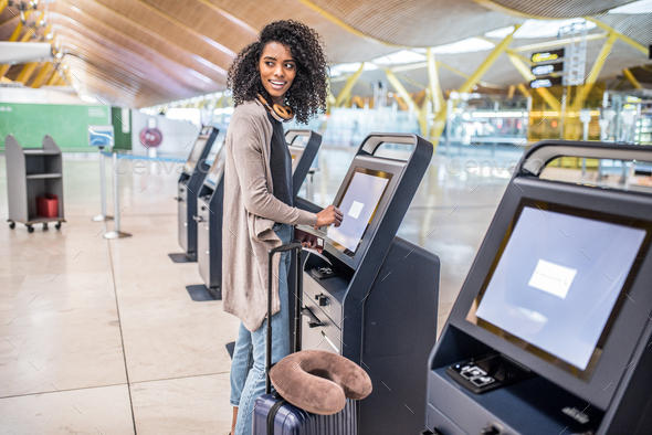 happy black woman using the check-in machine at the airport gett - Stock Photo - Images