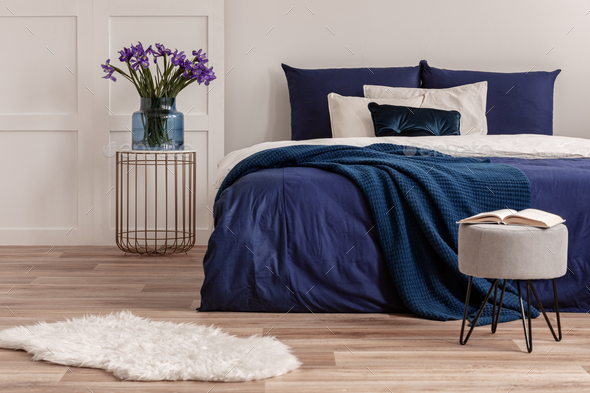 Purple flowers in blue glass vase on stylish bedside table next to king size bed - Stock Photo - Images