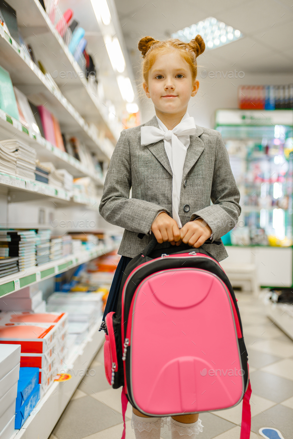 Schoolgirl with backpack in hand, stationery store - Stock Photo - Images