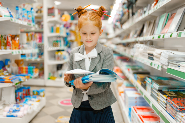 Little school girl in stationery store - Stock Photo - Images