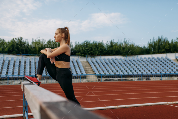 Female runner, stretching workout on stadium - Stock Photo - Images