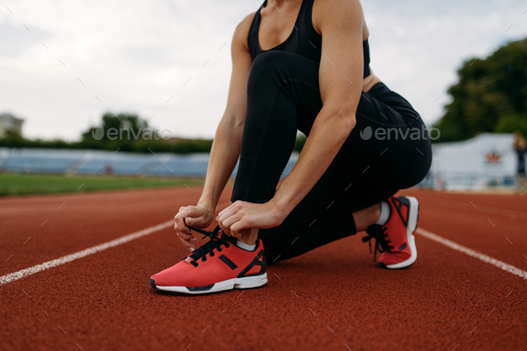 Female runner tying her shoelaces on stadium - Stock Photo - Images