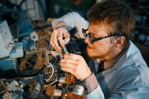 Scientist prototyping electrical device in lab - Stock Photo - Images