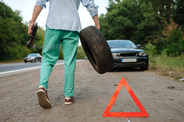 Car breakdown, man puts the spare tyre - Stock Photo - Images
