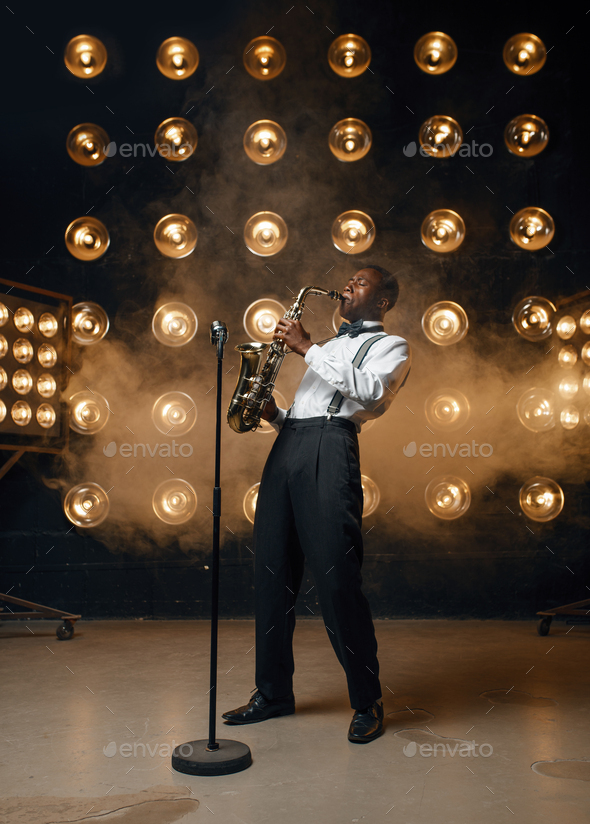 Male jazzman plays the saxophone on stage - Stock Photo - Images