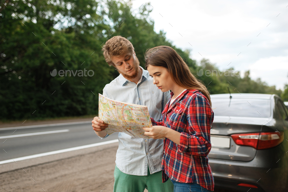Car tourists looking on map, road travel - Stock Photo - Images