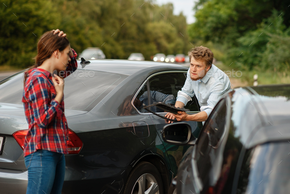 Male and female drivers on road, car accident - Stock Photo - Images