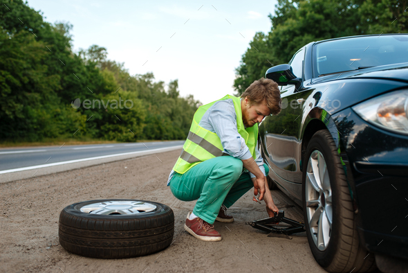 Car breakdown, young man repairing flat tyre - Stock Photo - Images