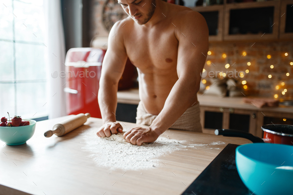 Muscular husband in underwear cooking on kitchen - Stock Photo - Images