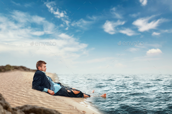 Businessman resting on the beach, lost island - Stock Photo - Images