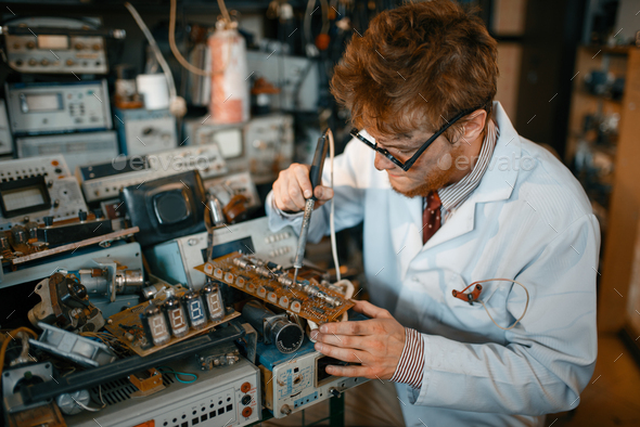 Strange scientist soldering chips, test in lab - Stock Photo - Images