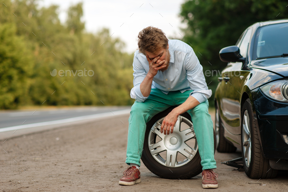 Car breakdown, tired man sitting on spare tyre - Stock Photo - Images