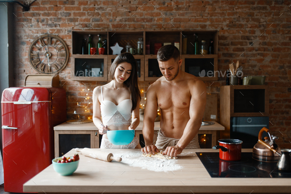 Young couple in underwear cooking on the kitchen - Stock Photo - Images