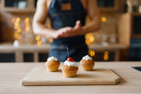 Naked man in apron cooking cakes with cherry - Stock Photo - Images