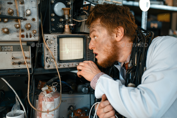 Engineer looks on oscilloscope display in lab - Stock Photo - Images