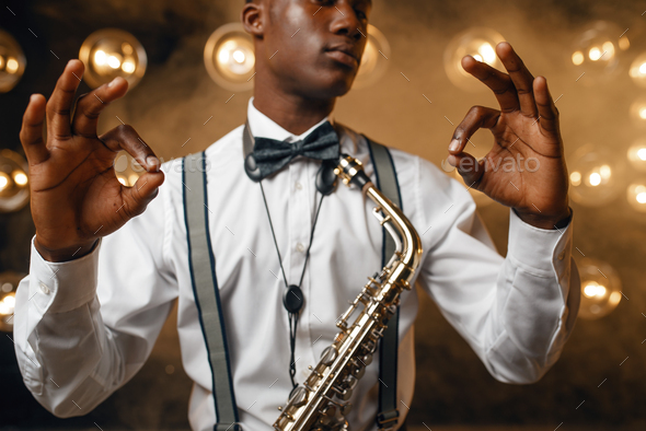 Black jazz performer with saxophone shows OK sign - Stock Photo - Images