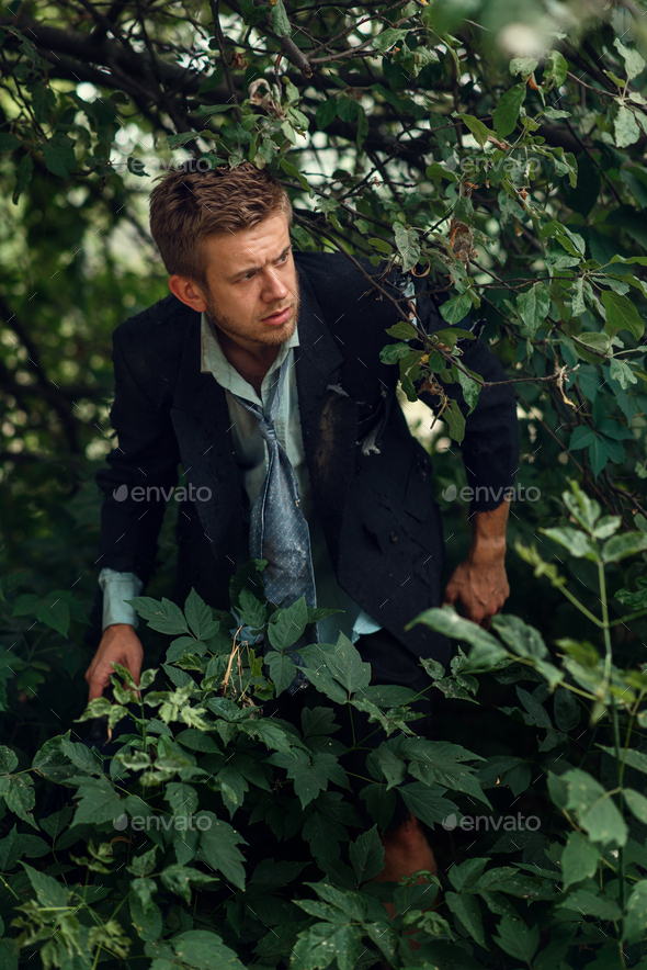 Alone businessman in torn suit on desert island - Stock Photo - Images