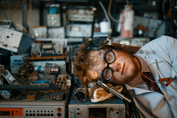 Strange engineer sleeping on devices in lab - Stock Photo - Images