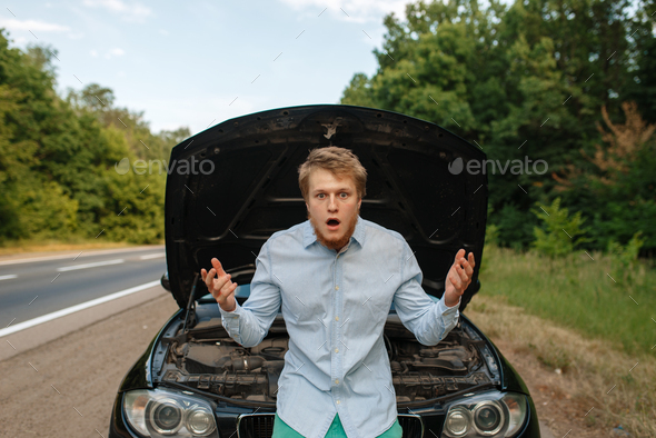 Tired young man at the opened hood, car breakdown - Stock Photo - Images