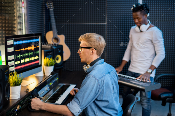 Serious man in denim shirt working with sound waveforms in studio of records - Stock Photo - Images