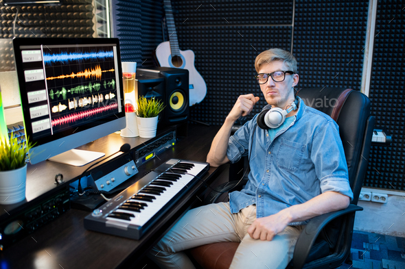 Serious young male deejay in casualwear sitting in armchair by workplace - Stock Photo - Images