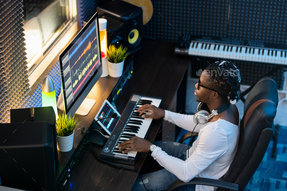 Young musician of African ethnicity sitting by workplace in studio of recording - Stock Photo - Images
