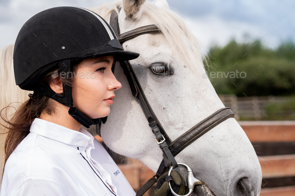 Young calm female in white shirt and equestrian helmet standing by racehorse - Stock Photo - Images