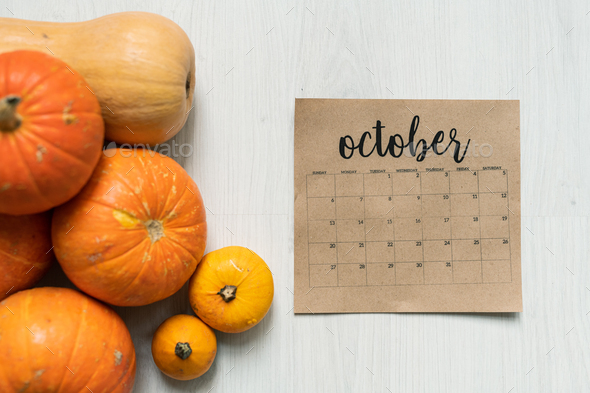 Overview of October calendar sheet and group of ripe orange and yellow pumpkins - Stock Photo - Images