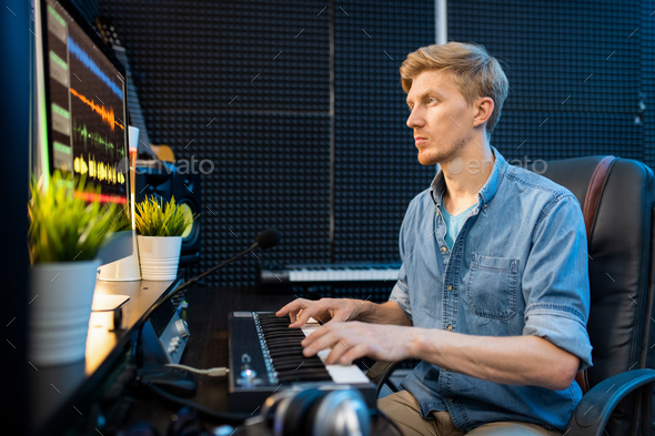 Young man looking at computer screen while pressing keys of piano keyboard - Stock Photo - Images