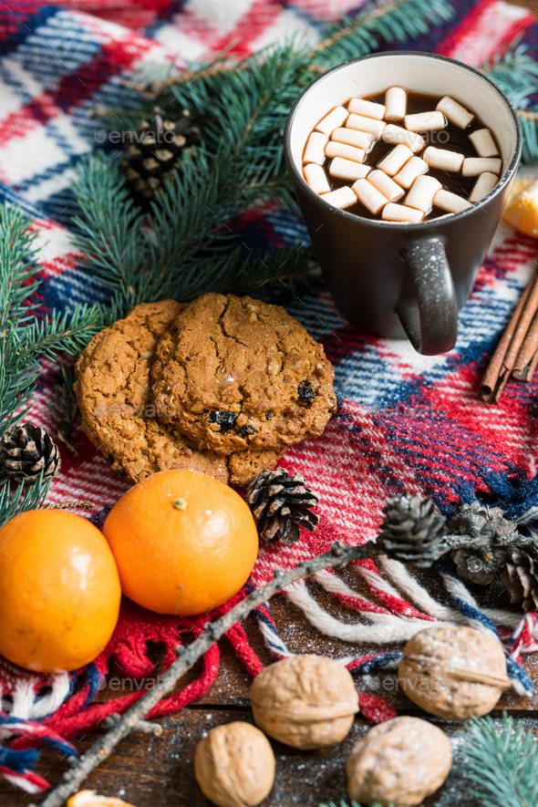 Hot drink with marshmallows, walnuts, mandarines and cookies on warm scarf - Stock Photo - Images