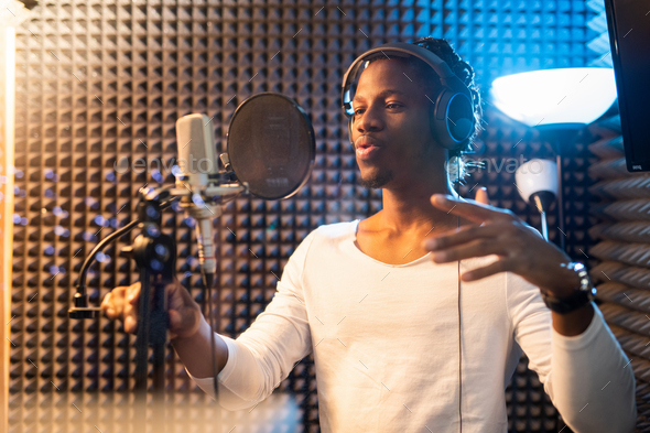 Young African man in white t-shirt and headphones performing songs in studio - Stock Photo - Images
