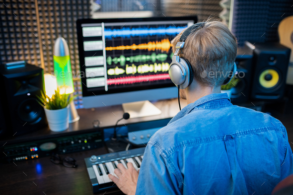 Rear view of young man in headphones making music by computer monitor - Stock Photo - Images
