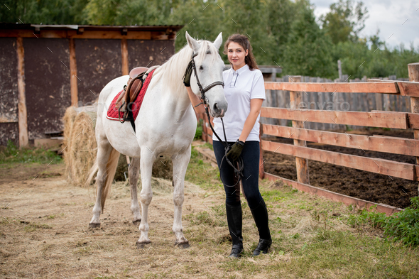 Young active woman chilling out with white purebred racehorse - Stock Photo - Images