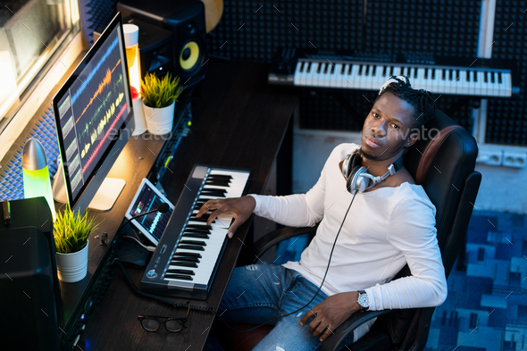 Young Afroamerican man in casualwear looking at you while sitting in studio - Stock Photo - Images
