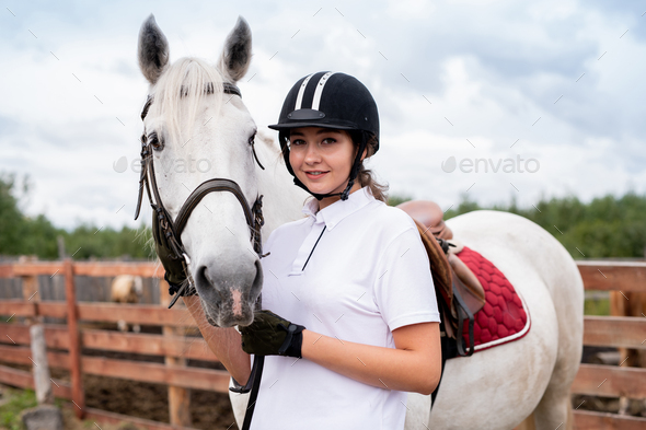 Young smiling woman in equestrian outfit standing close to white racehorse - Stock Photo - Images