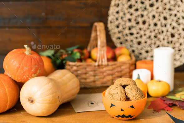 Group of ripe pumpkins, orange halloween plastic bowl with cookies - Stock Photo - Images