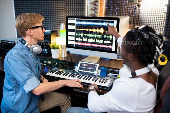 One of contemporary musicians pointing at sound waveform on computer screen - Stock Photo - Images