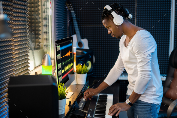 Confident young musician with headphones listening to mixed sounds in headphones - Stock Photo - Images