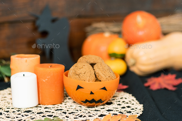 Halloween plastic bowl with cookies and three candles on white knitted napkin - Stock Photo - Images