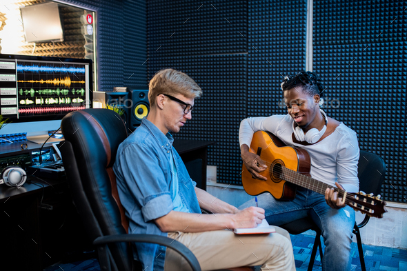 Two young multicultural men working over new song in sound recording studio - Stock Photo - Images