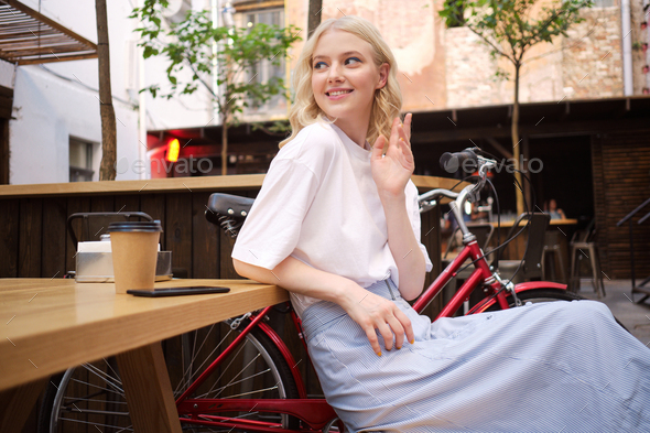 Beautiful flirty blond girl happily greeting someone resting with coffee in courtyard of cafe - Stock Photo - Images