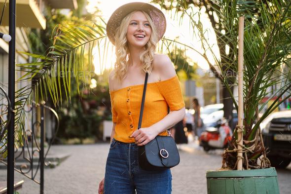 Beautiful romantic tourist blond girl in hat joyfully walking looking away on city street - Stock Photo - Images