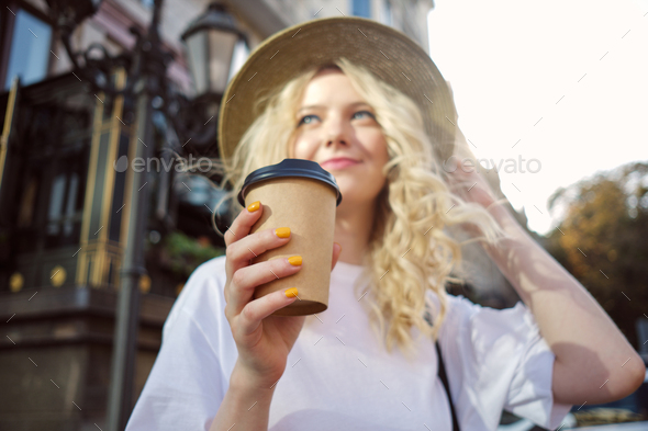 Fuzzy attractive casual blond girl in hat dreamily looking away with coffee to go on city street - Stock Photo - Images