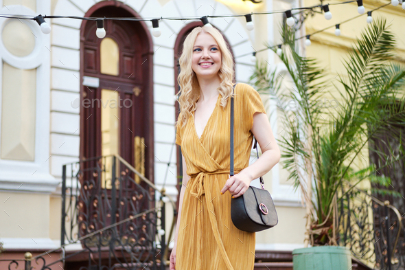 Beautiful elegant smiling blond girl in dress with bag happily looking away walking on city street - Stock Photo - Images